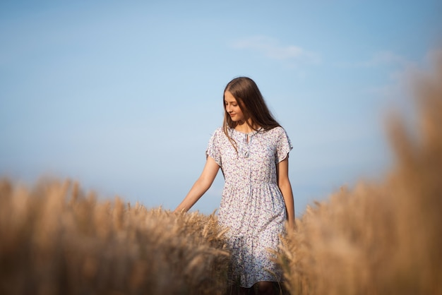 Portrait d'une jeune fille en robe blanche dans le champ de blé