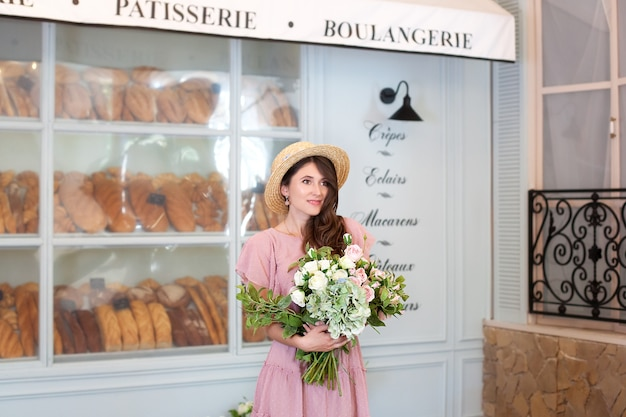 Portrait jeune fille en robe et chapeau de paille tenant un bouquet de fleurs contre une boulangerie française