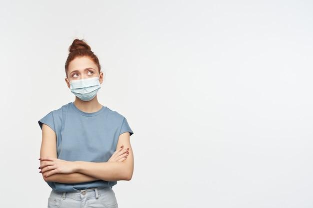Portrait de jeune fille rousse aux cheveux rassemblés en chignon. porter un t-shirt bleu et un masque protecteur. les mains croisées. regarder dans le coin supérieur droit à l'espace de copie, isolé sur un mur blanc