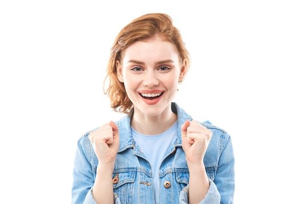 Portrait d'une jeune fille rousse sur fond blanc isolé en jeans. regarde la caméra en se tenant la main devant toi dans un poing