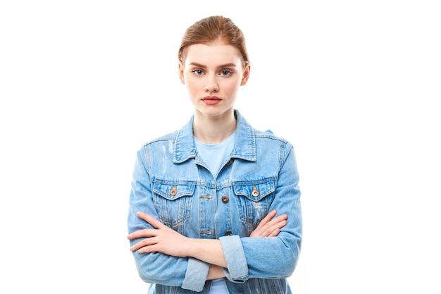Portrait d'une jeune fille rousse sur fond blanc isolé en jeans. regarde dans la caméra