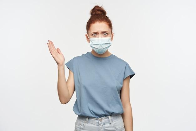 Portrait de jeune fille rousse fronçant les sourcils, choquée avec les cheveux rassemblés en un chignon. porter un t-shirt bleu, un jean et un masque protecteur. levez la main. isolé sur mur blanc