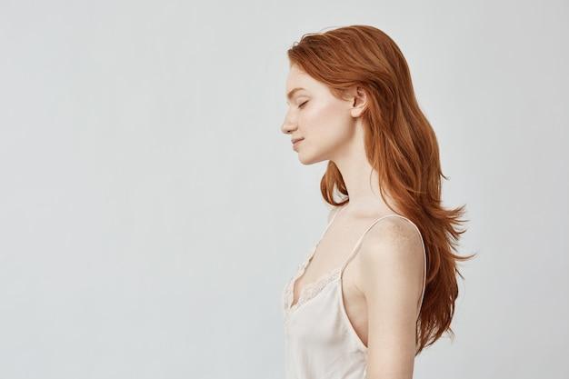 Portrait de jeune fille rousse de profil avec les yeux fermés en souriant.
