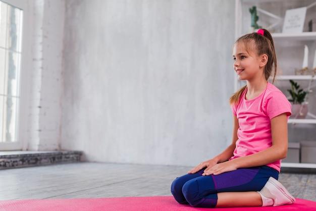 Portrait d'une jeune fille souriante assise sur un tapis rose à la recherche de suite