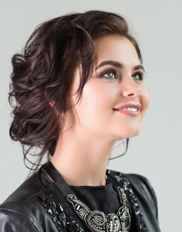 Portrait d'une jeune fille souriante aux cheveux bruns et les yeux gris.