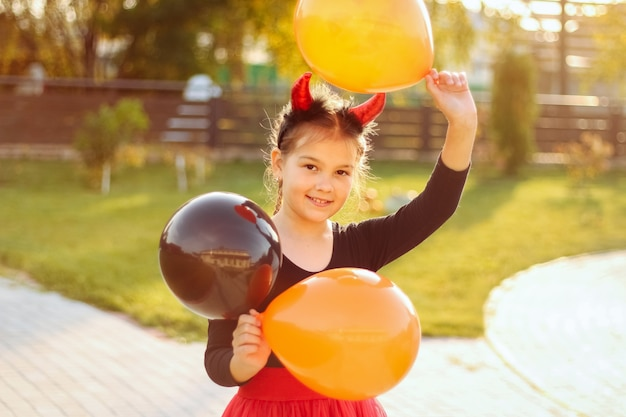 Portrait d'une jeune fille souriante aux cheveux noirs dans un costume d'halloween tenant des ballons orange et noirs à l'extérieur.