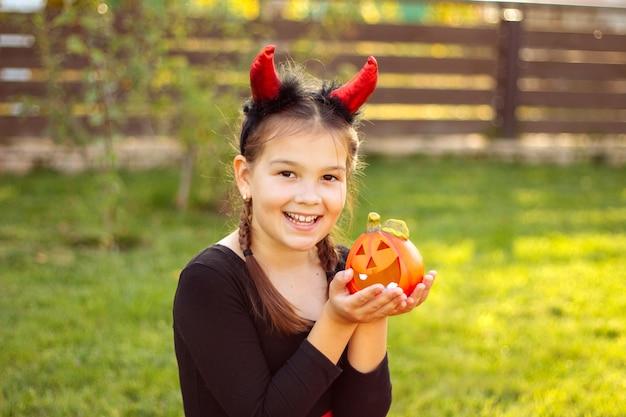 Portrait d'une jeune fille souriante aux cheveux noirs dans un costume d'halloween, tenant une citrouille orange à l'extérieur.