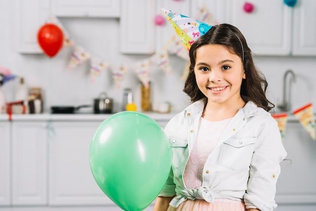 Portrait d'une jeune fille souriante avec ballon vert, regardant la caméra