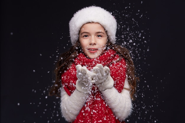 Portrait de jeune fille souriante belle en bonnet rouge sur un fond sombre