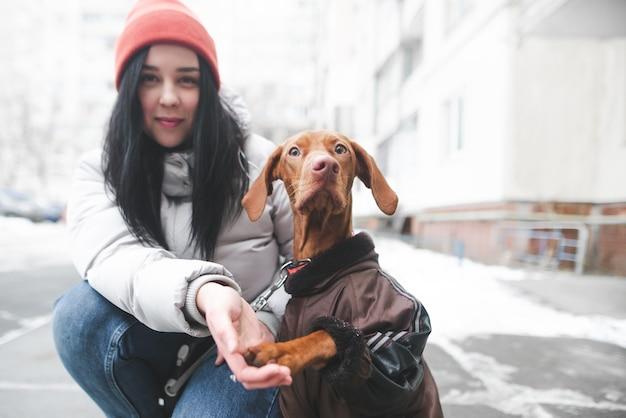 Portrait d'une jeune fille souriante et un chien dans des vêtements chauds assis en hiver dans la rue
