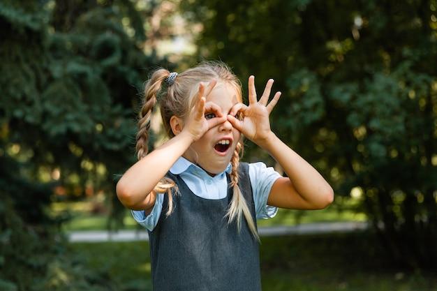 Portrait d'une jeune fille souriante choquée excitée tenant ses mains sur son visage.