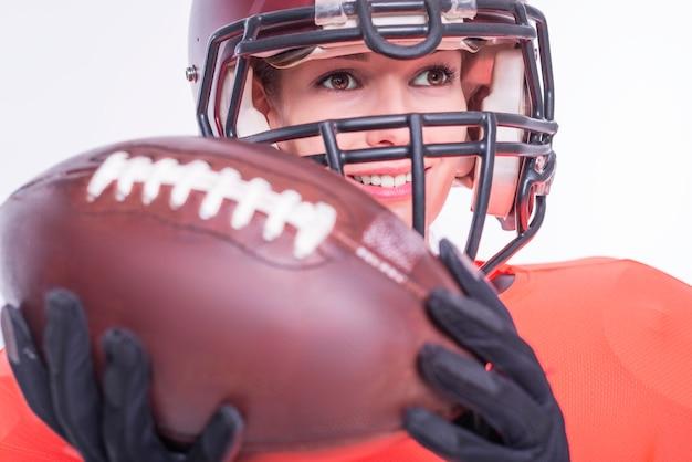 Portrait d'une jeune fille souriante dans l'uniforme d'un joueur de l'équipe de football américain. fond blanc. notion de sport. technique mixte