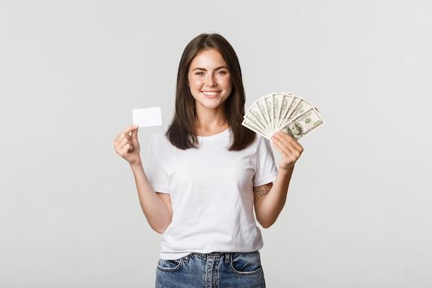 Portrait de jeune fille souriante excitée tenant de l'argent et une carte de crédit, blanc.