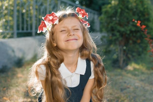 Portrait de jeune fille souriante avec guirlande de fleurs roses