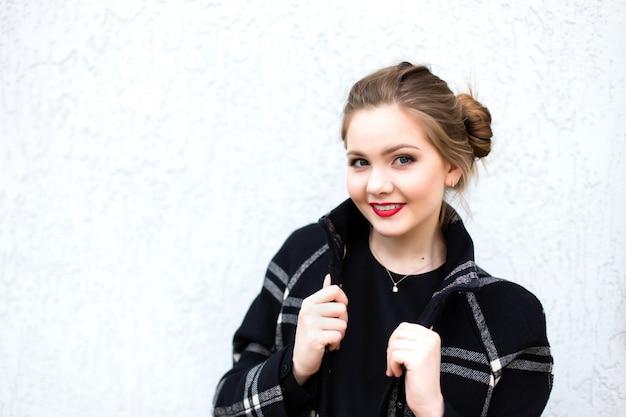 Portrait d'une jeune fille souriante en haute clé contre un mur blanc