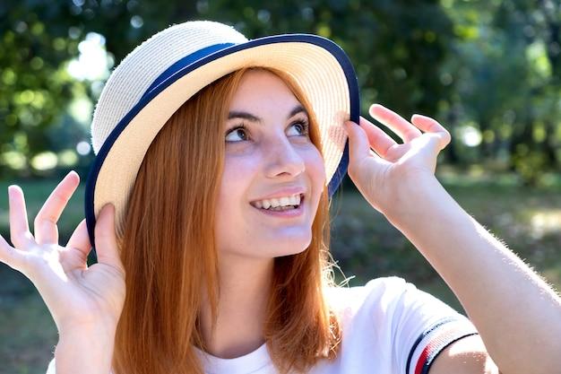 Portrait de jeune fille souriante heureuse aux cheveux rouges et au chapeau jaune à l'extérieur dans le parc de l'été.