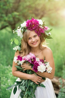 Portrait d'une jeune fille souriante heureuse avec une couronne de fleurs et un bouquet de pivoines d'apparence caucasienne