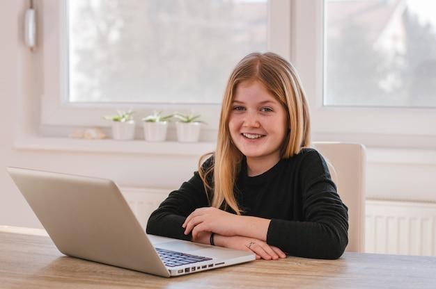 Portrait de jeune fille souriante avec ordinateur à la maison