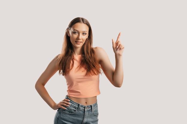 Portrait d'une jeune fille souriante pointant le doigt sur le côté sur un fond blanc isolé. la femme positive indique une idée, un endroit pour la publicité