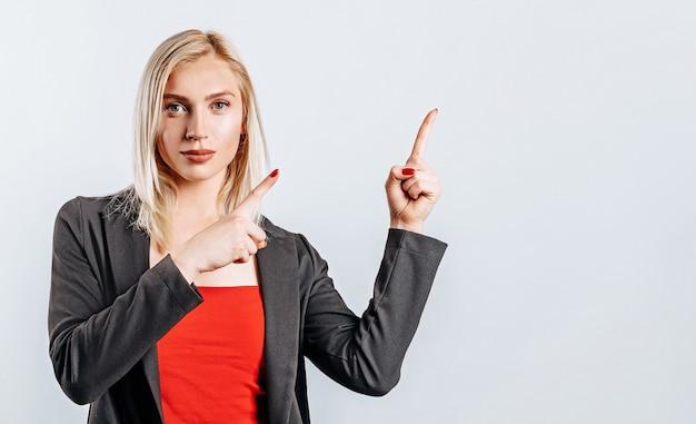 Portrait d'une jeune fille souriante pointant le doigt vers le haut à copyspace isolé sur fond blanc