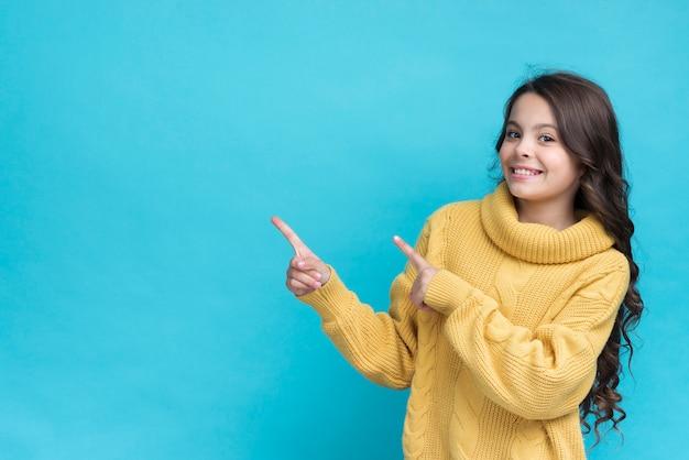Portrait de jeune fille souriante pointant