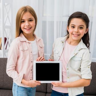 Portrait d'une jeune fille souriante, portant une veste en jean montrant une tablette numérique