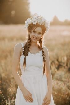 Portrait de jeune fille souriante en robe blanche avec couronne florale et tresses en été au coucher du soleil sur le terrain