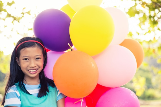 Portrait de jeune fille souriante tenant des ballons dans le parc