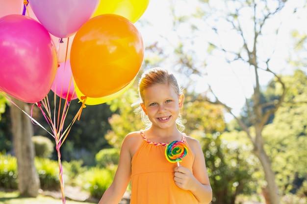 Portrait de jeune fille souriante tenant des ballons et sucette dans le parc