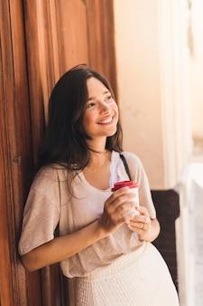 Portrait d'une jeune fille souriante tenant une tasse de café jetable