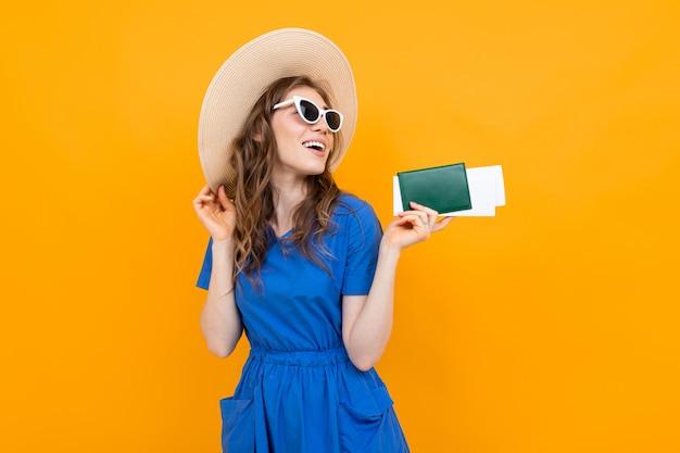 Portrait d'une jeune fille sur une surface orange avec un passeport et des billets d'avion