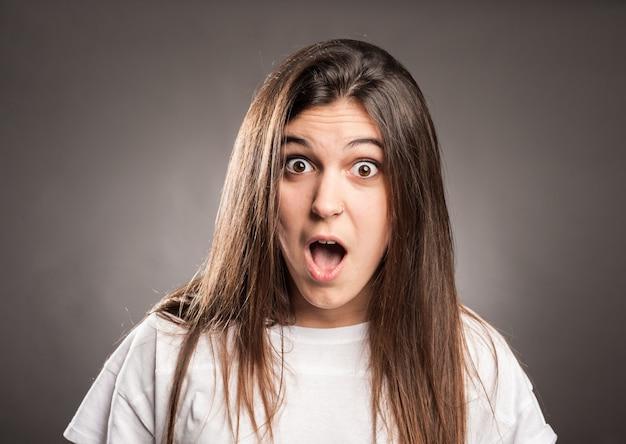 Portrait de jeune fille surprise sur fond gris