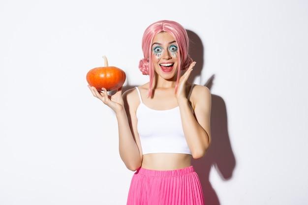 Portrait de jeune fille surprise en perruque rose, tenant la citrouille et à la recherche excitée, célébrant l'halloween, debout.