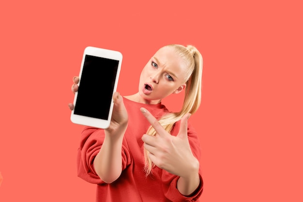 Portrait d'une jeune fille surprise, souriante, heureuse, étonnée montrant un téléphone mobile à écran blanc isolé sur fond de corail.