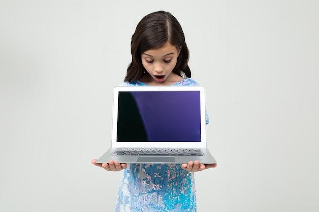 Portrait d'une jeune fille surprise tenant un ordinateur portable avec un écran vide pour insérer un site web sur un mur blanc