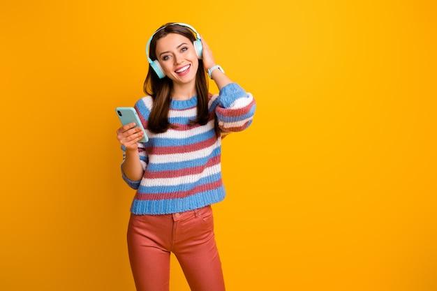 Portrait de jeune fille tenant dans les mains lecteur mp3 écouter de la musique dans des écouteurs