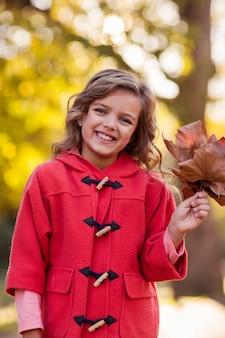 Portrait de jeune fille tenant des feuilles d'automne au parc
