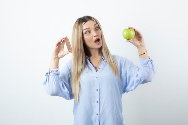 Portrait d'une jeune fille tenant une pomme verte avec une barre de chocolat contre un mur blanc