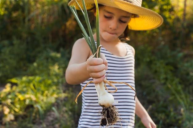 Portrait de jeune fille tenant récolté des oignons de printemps