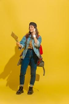Portrait d'une jeune fille de touriste caucasienne joyeuse isolée sur jaune