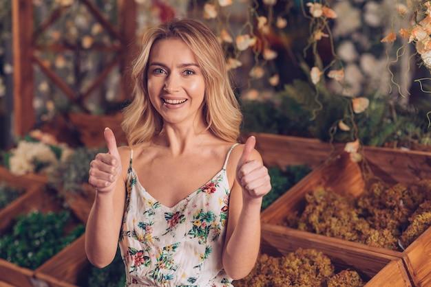 Portrait d'une jeune fleuriste blonde montrant le pouce en haut signe avec deux mains