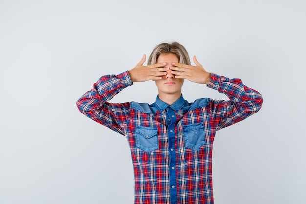 Portrait de jeune garçon adolescent couvrant les yeux avec les mains en chemise à carreaux et à la vue de face effrayée
