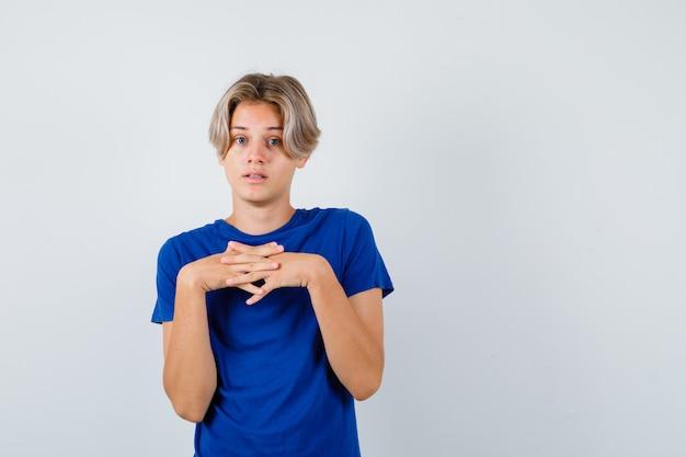 Portrait de jeune garçon adolescent gardant les doigts entrelacés sur la poitrine en t-shirt bleu et à la vue de face désemparée