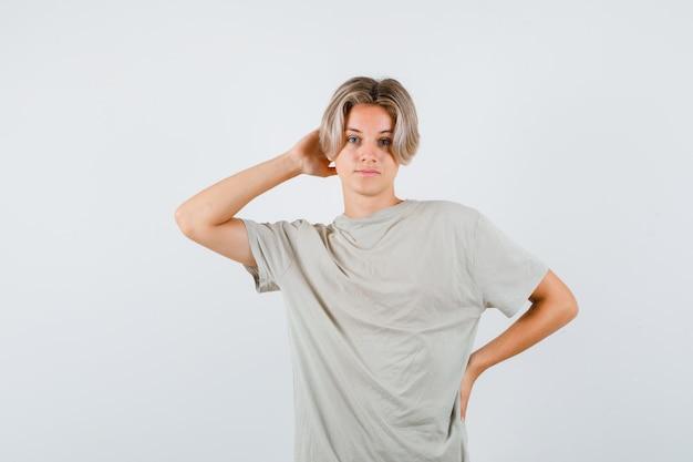 Portrait de jeune garçon adolescent gardant la main derrière la tête en t-shirt et à la vue de face confiant