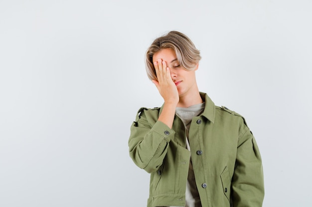 Portrait de jeune garçon adolescent gardant la main sur le visage en t-shirt, veste et à la vue de face fatigué