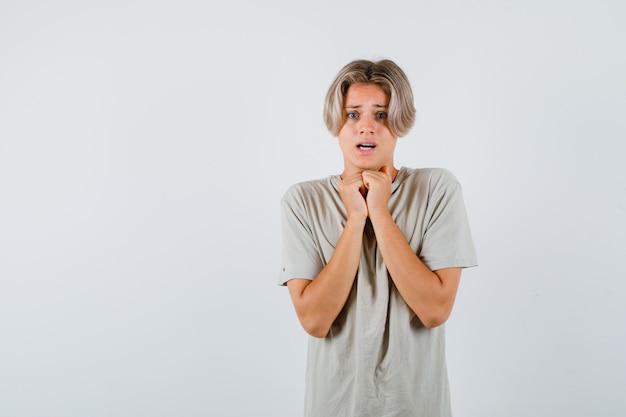 Portrait de jeune garçon adolescent gardant les mains sous le menton en t-shirt et à la vue de face effrayée