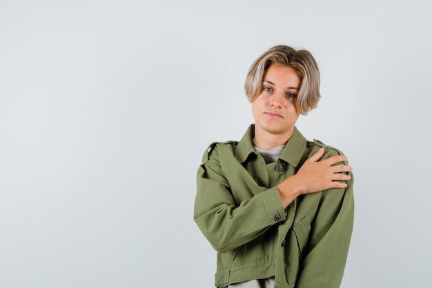 Portrait de jeune garçon adolescent avec la main sur l'épaule en veste verte et à la vue de face confiant