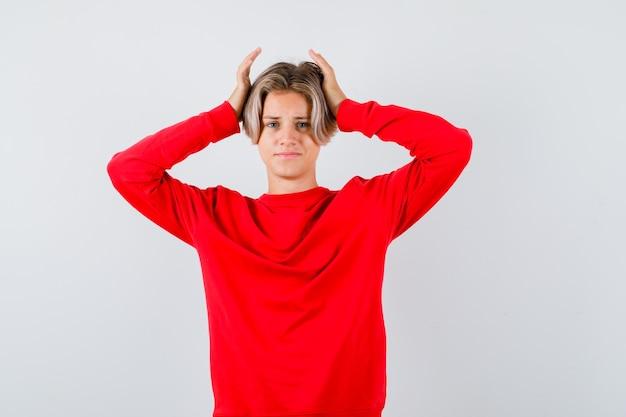Portrait de jeune garçon adolescent avec les mains sur la tête en pull rouge et à la vue de face oublieux