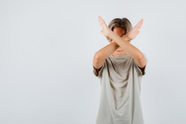 Portrait d'un jeune garçon adolescent montrant un geste d'arrêt en t-shirt et regardant une vue de face résolue