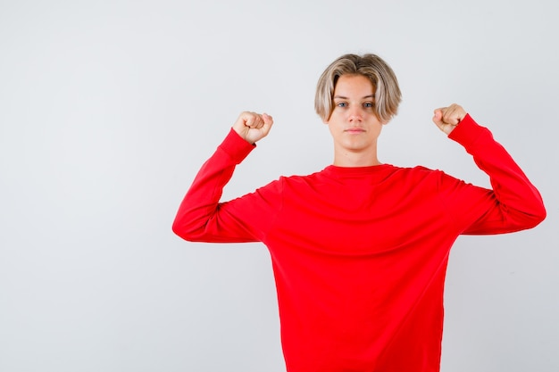 Portrait de jeune garçon adolescent montrant les muscles des bras en pull rouge et à la vue de face confiant